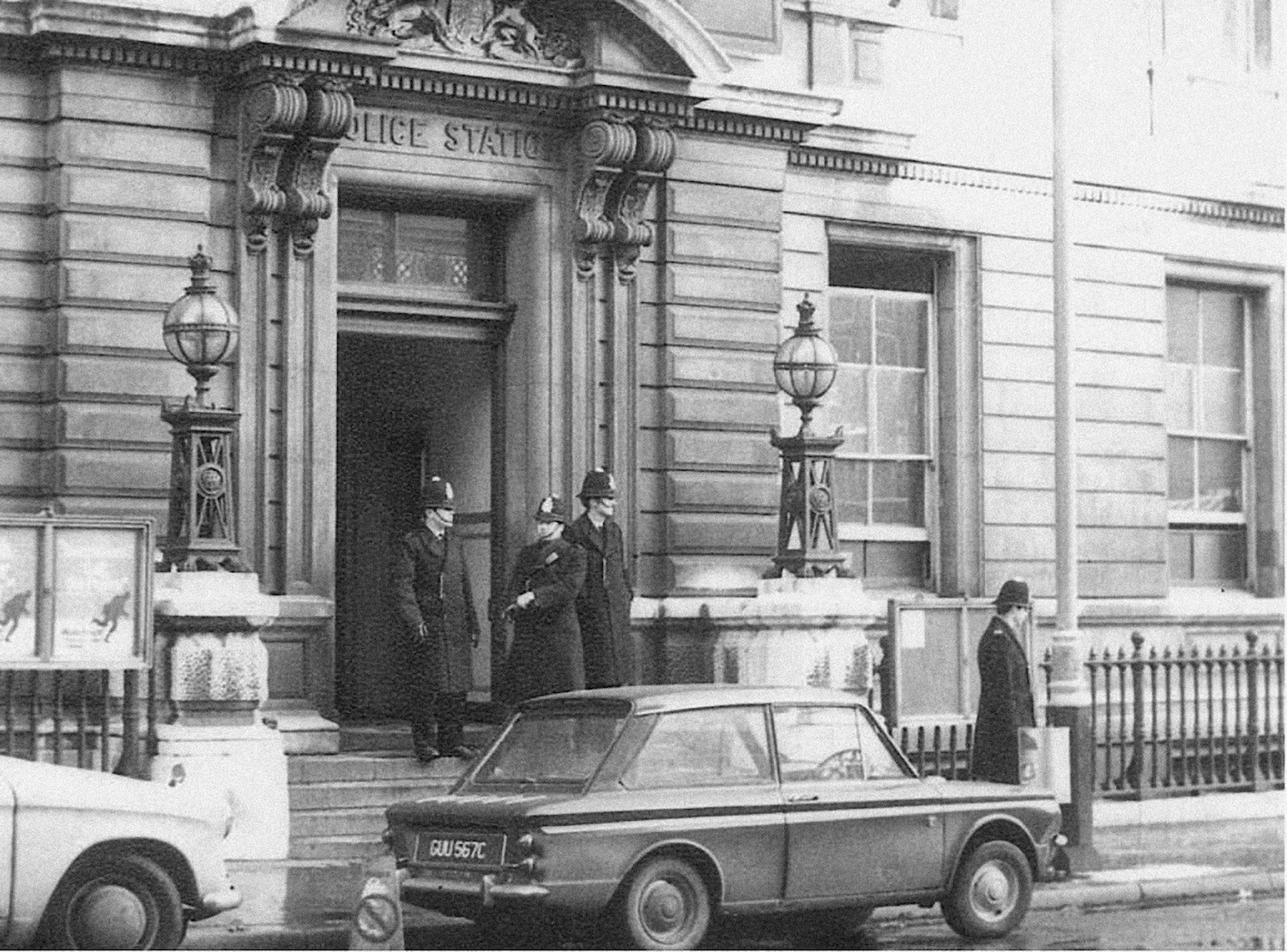 Policemen standing outside building with vintage car in street